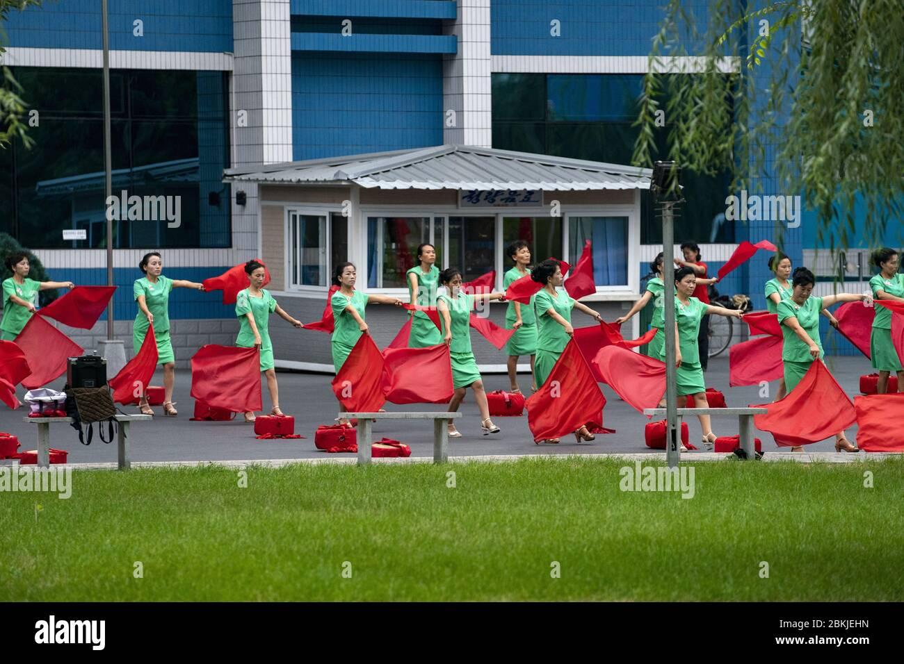 Corea del Norte, Pyongyang, mujeres sin empleo que animan a la gente que trabaja Foto de stock