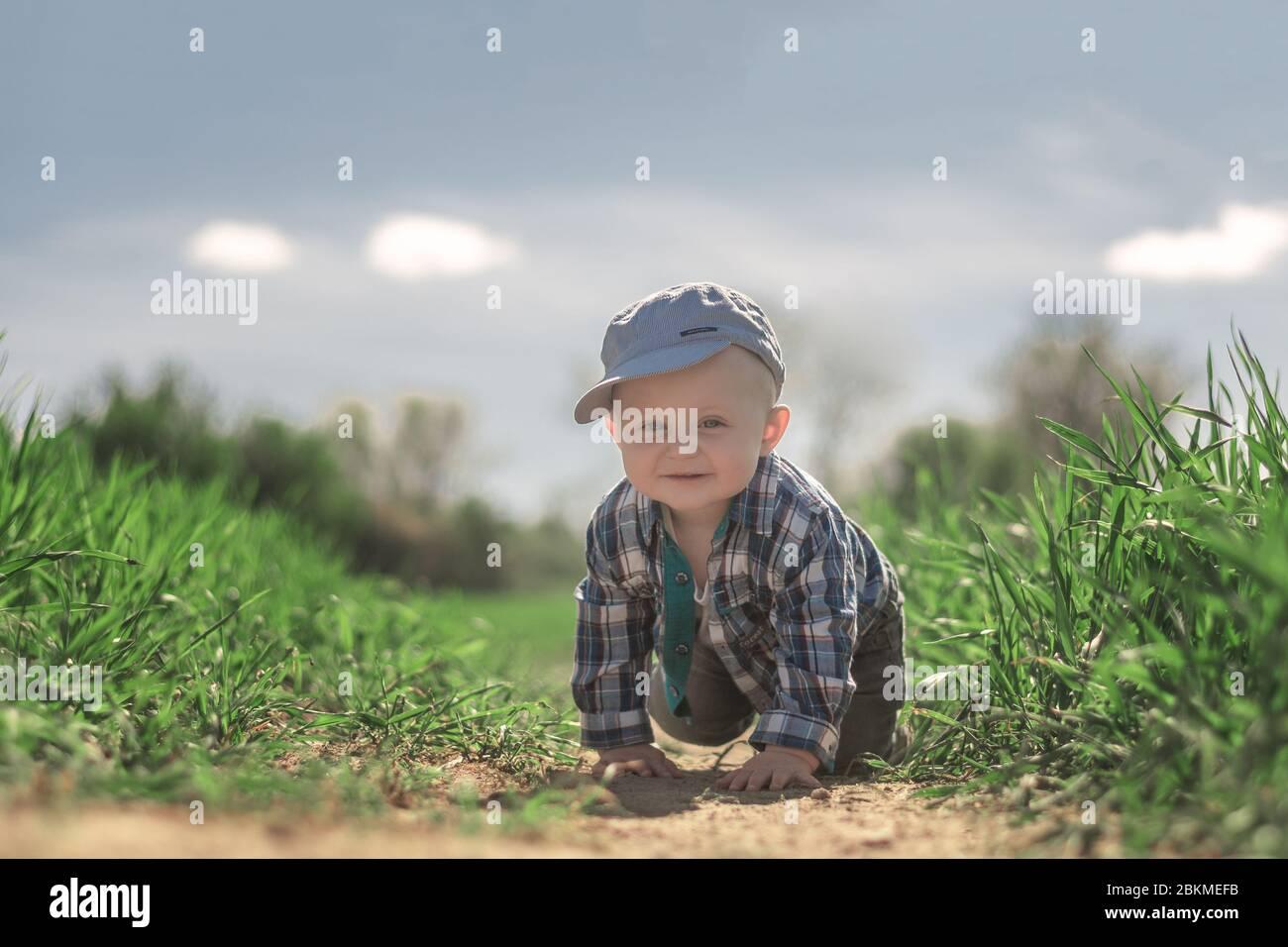 Un pequeño niño caucásico con ojos azules en una gorra de béisbol y camisa de cuadros arrastrándose en el surco de un campo con grano en crecimiento. Foto de stock