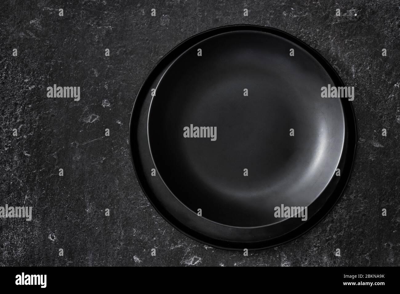 Vista superior de planchas negras vacías sobre fondo negro Foto de stock