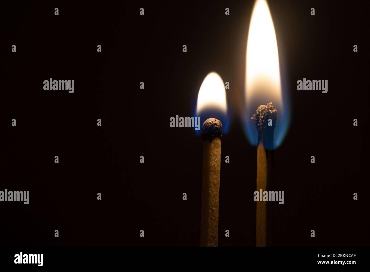 Pasión en llamas. Pareja-de-cerillas-quemandose-junto-con-la-llama-de-calor-aislada-sobre-un-fondo-negro-2bknca9