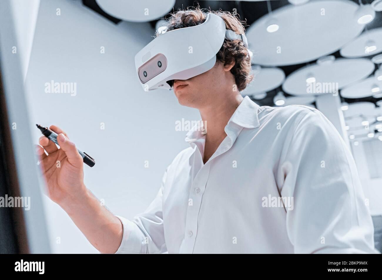 Hombre joven con gafas de realidad Virtual escribiendo en Flipchart durante la presentación en línea en escena sin espectadores. Distanciamiento social. Quédate en casa Foto de stock
