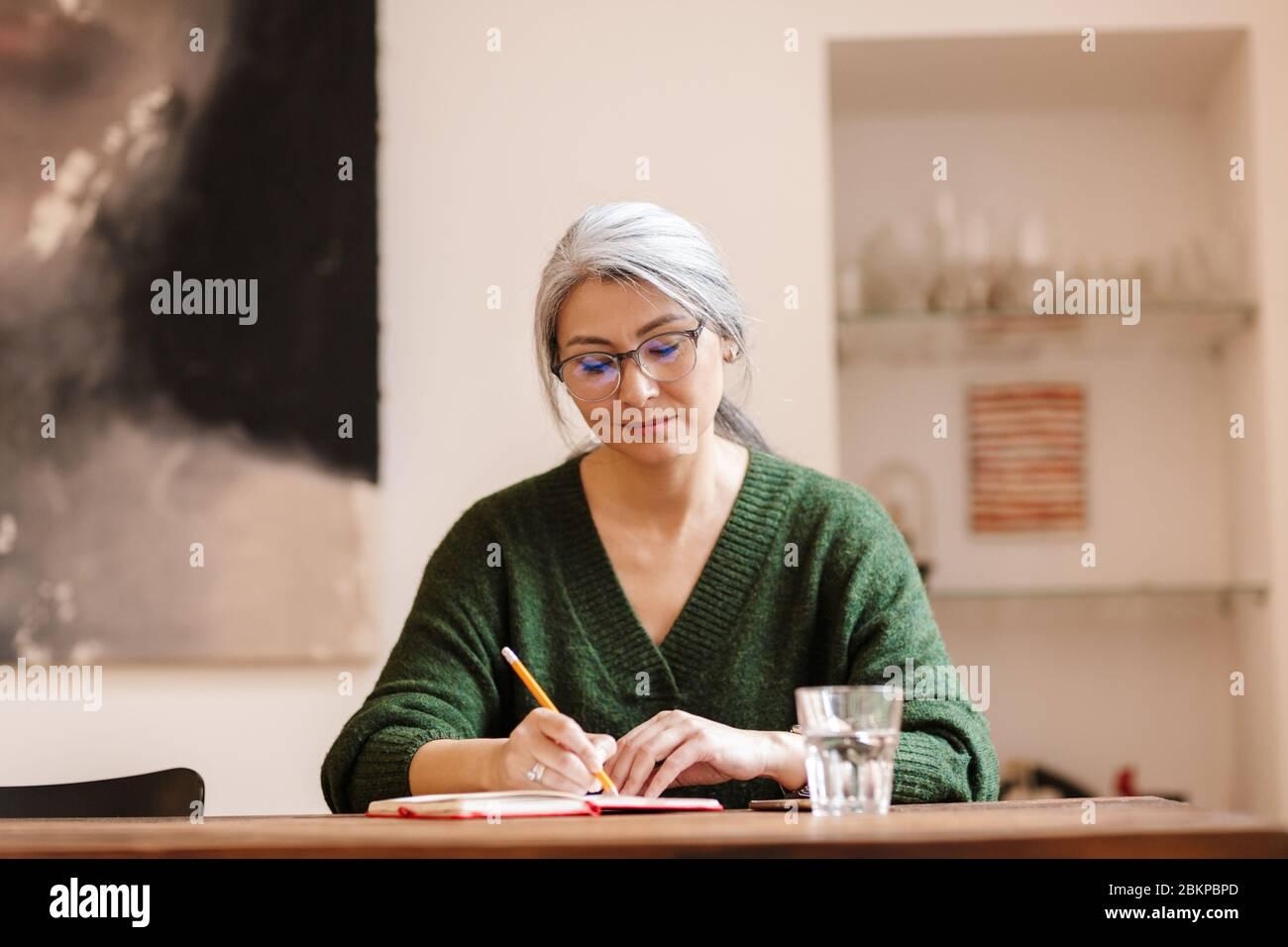 Foto de mujer madura optimista concentrada hermosa de pelo gris en interiores escribir notas. Foto de stock