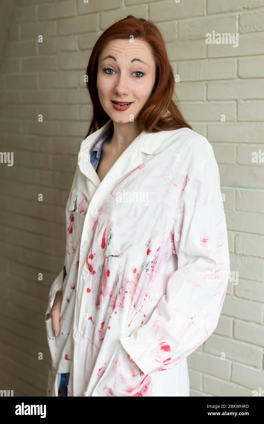 Retrato de una niña de pelo rojo en una bata pintada de blanco sobre un fondo de pared de ladrillo Foto de stock