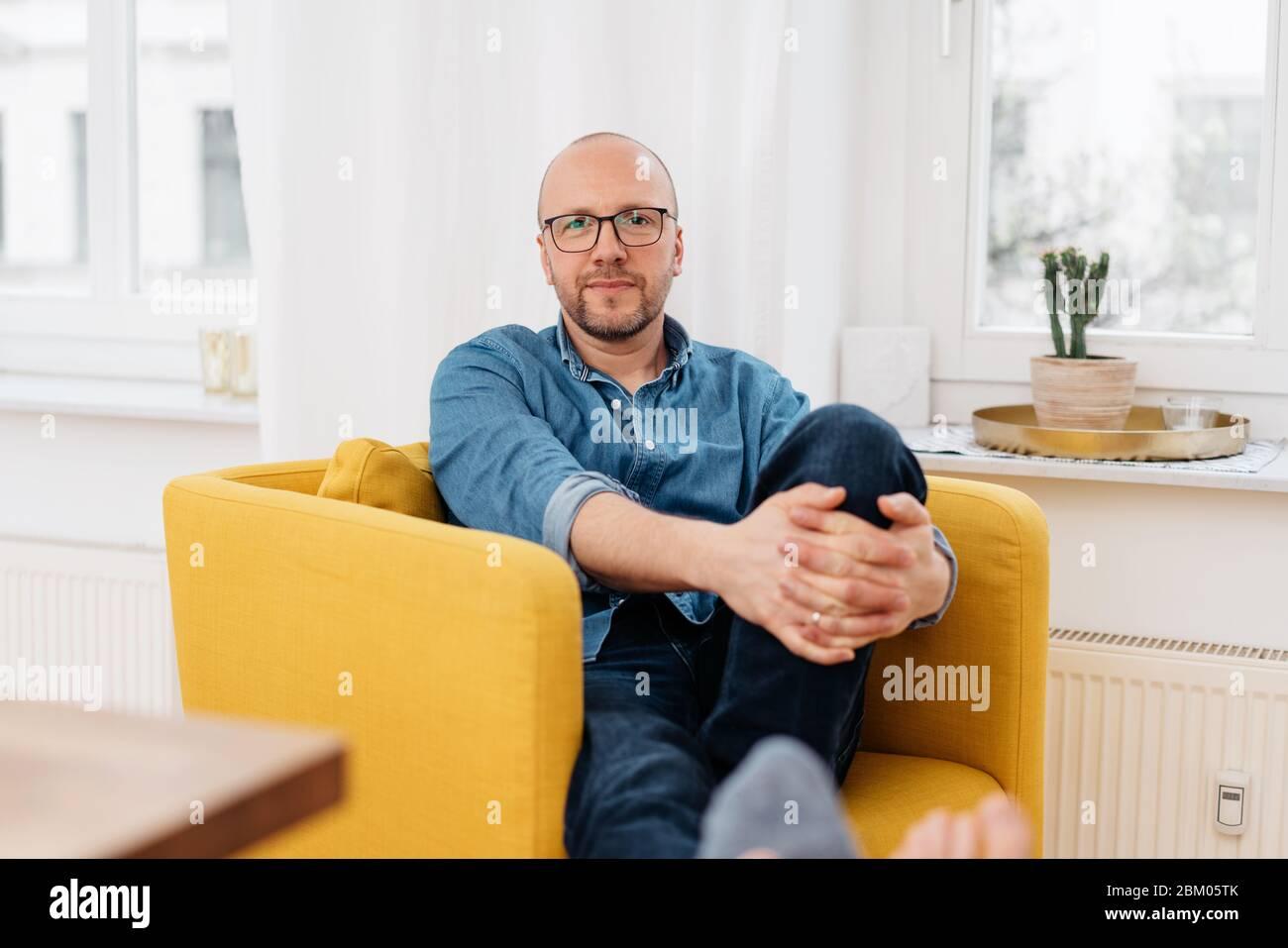 Hombre de mediana edad con gafas relajándose en una silla amarilla de colores en casa mirando cuidadosamente la cámara Foto de stock