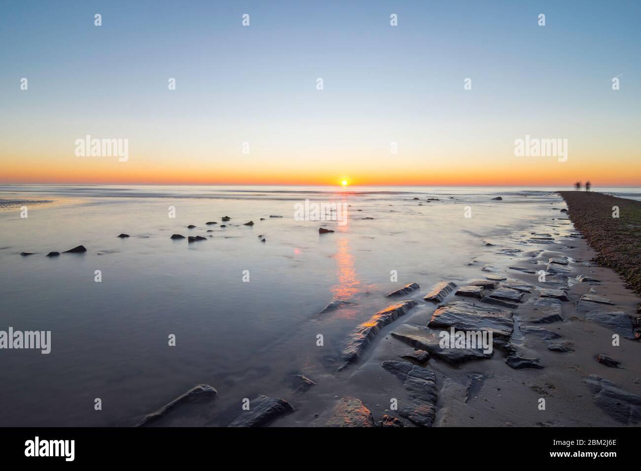 Ambiente nocturno sobre el muelle en el mar. Las piedras reflejan la luz de la noche y los últimos rayos del sol. La arena ondulada se puede ver a través del shal Foto de stock