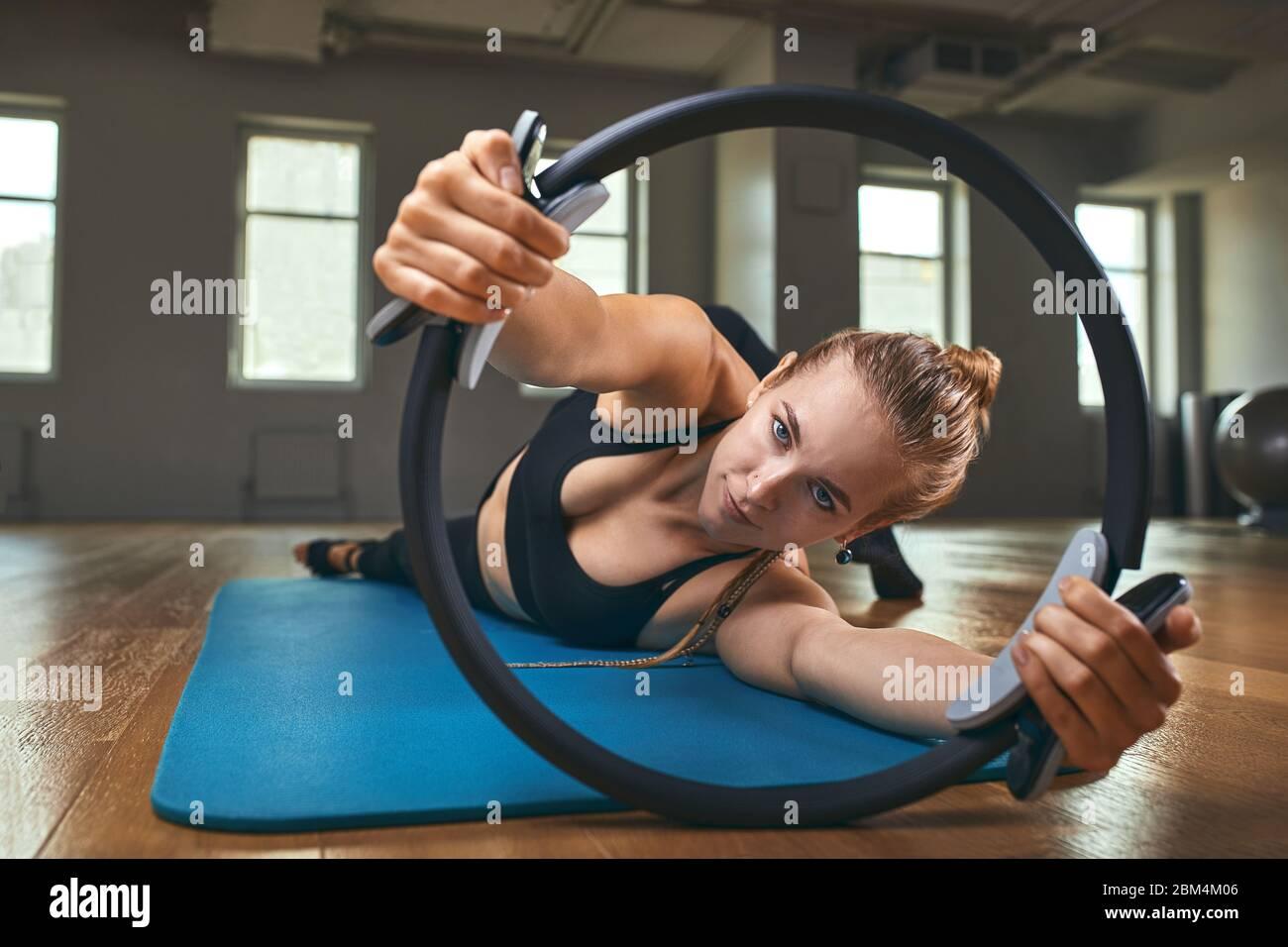 Joven modelo de fitness mujer atleta en sportswear haciendo ejercicios de estiramiento con expansor de caucho. Culturismo estilo de vida saludable concepto imagen Foto de stock