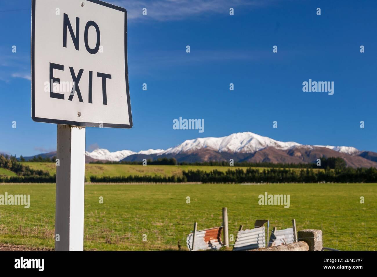 """Un cartel blanco pintado de """"no salir"""" advierte a los conductores de un no a través de la carretera que está por delante. Letreros blancos en un paisaje de luz con montañas y un cielo azul claro Foto de stock"""