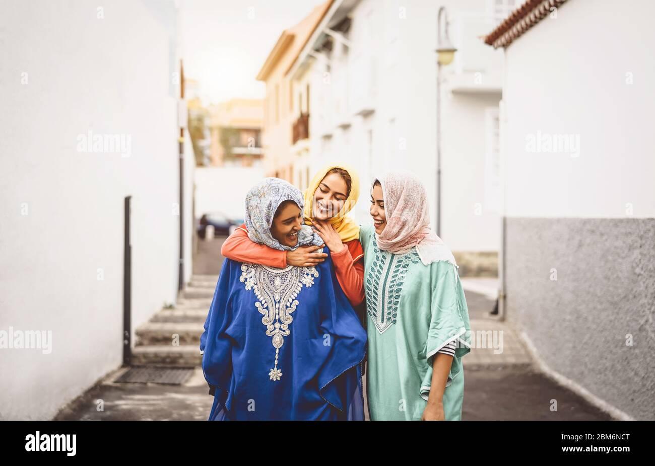 Feliz mujeres musulmanas caminando en el centro de la ciudad - Arabian niñas divirtiéndose gastar tiempo y riendo juntos outdoor Foto de stock
