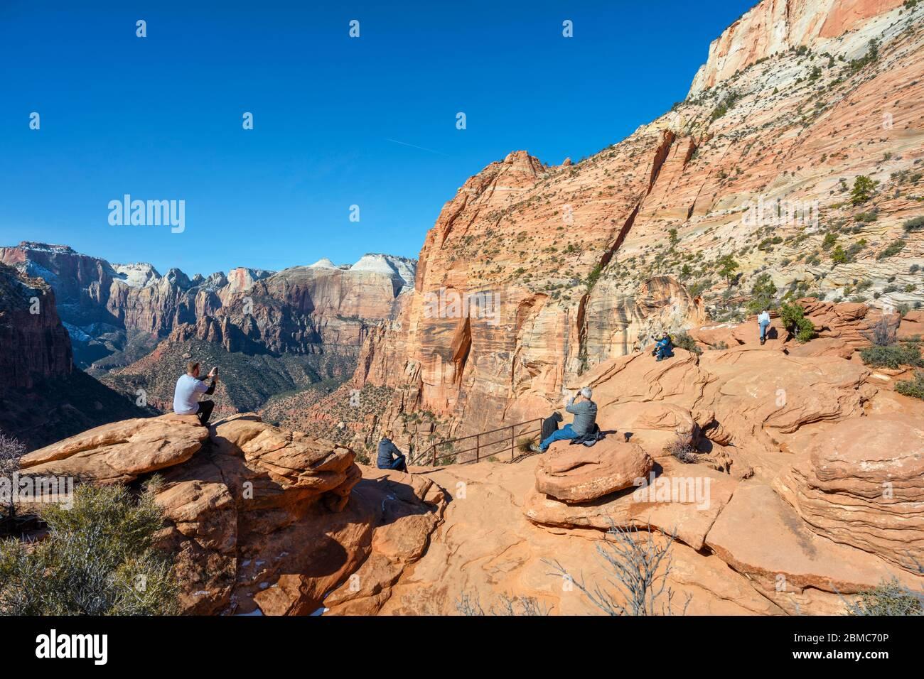 Los senderistas que miran hacia la vista del Cañón Zion desde el mirador del Cañón, el Parque Nacional Zion, Utah, Estados Unidos Foto de stock