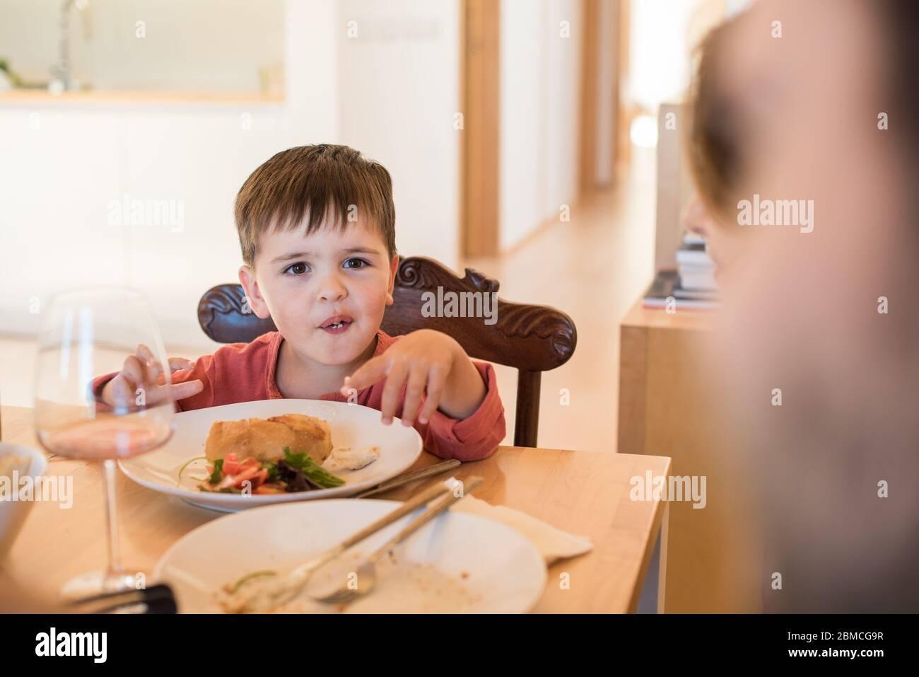 Familia joven con un niño pequeño sentado juntos para el almuerzo Foto de stock