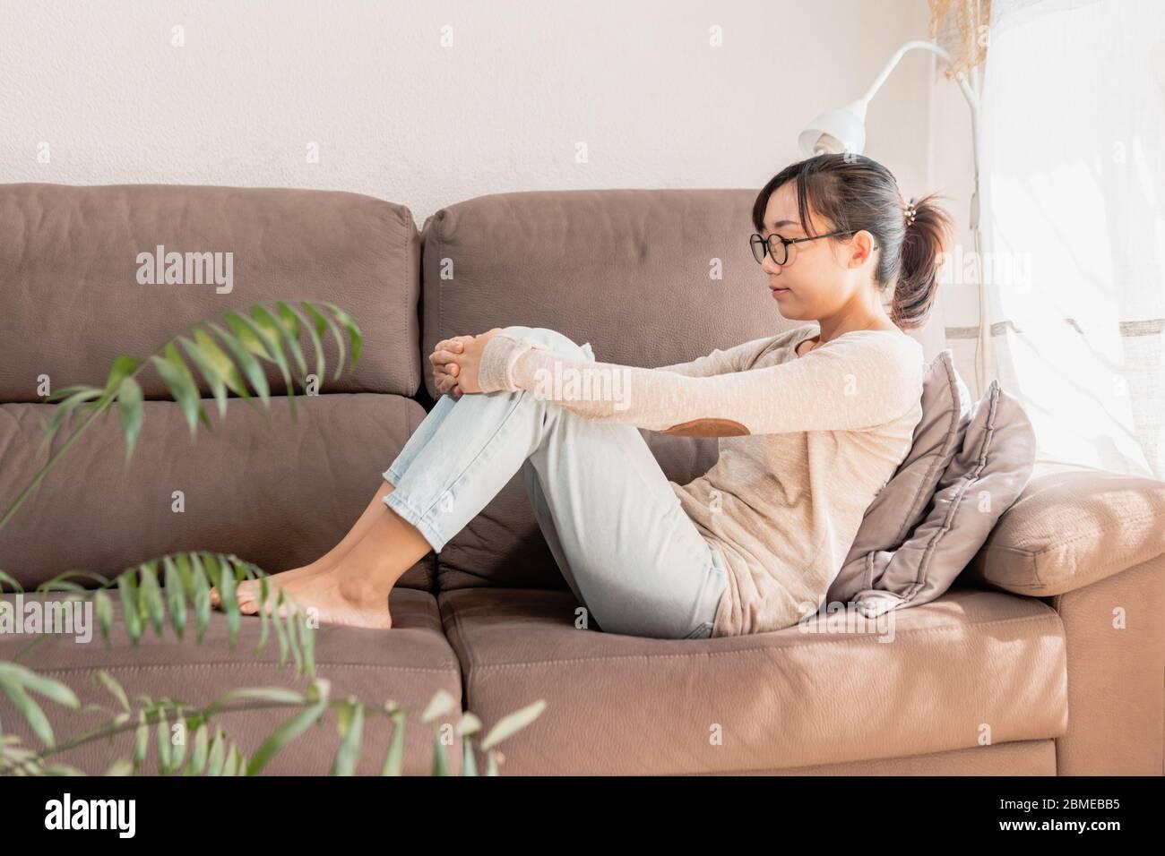 Mujer acostada en el sofá pensando y soñando despierto. Coronavirus permanecer en cuarentena en casa. Chica en el sofá relajante y meditando Foto de stock