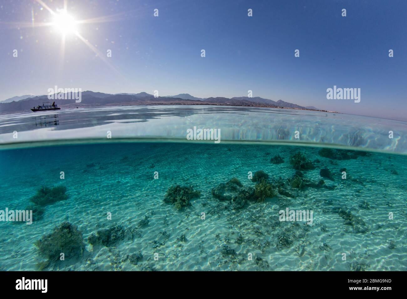 Sobre bajo la imagen dividida de aguas poco profundas de una vista costera típica a lo largo de la costa del Mar Rojo. Foto de stock