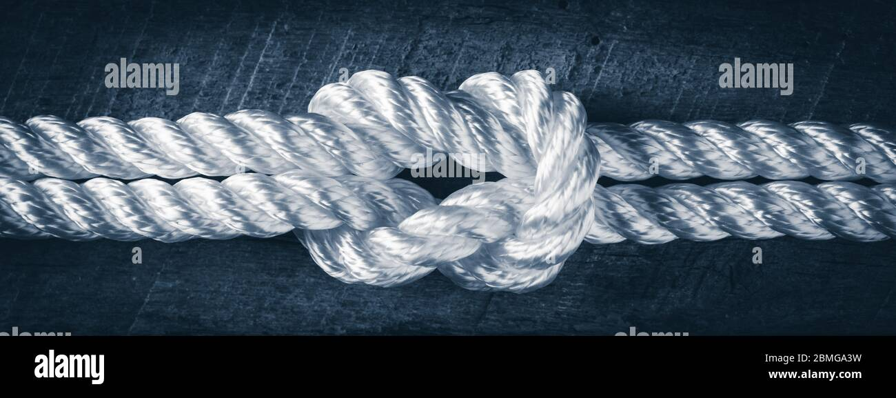 Primer plano de cuerda blanca unida en cubierta de madera del barco - la fuerza en concepto de la asociación Foto de stock