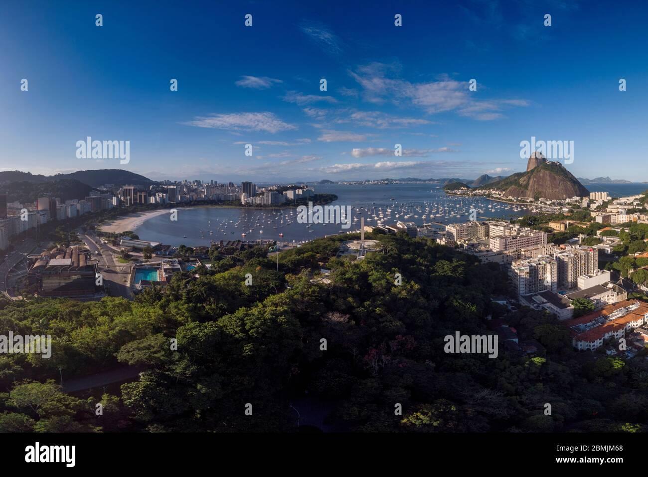 Playa Botafogo y montaña Sugarloaf a ambos lados del puerto de la bahía de Guanabara para los barcos de placer contra un cielo azul con el parque de la colina pasmado y vistas Foto de stock