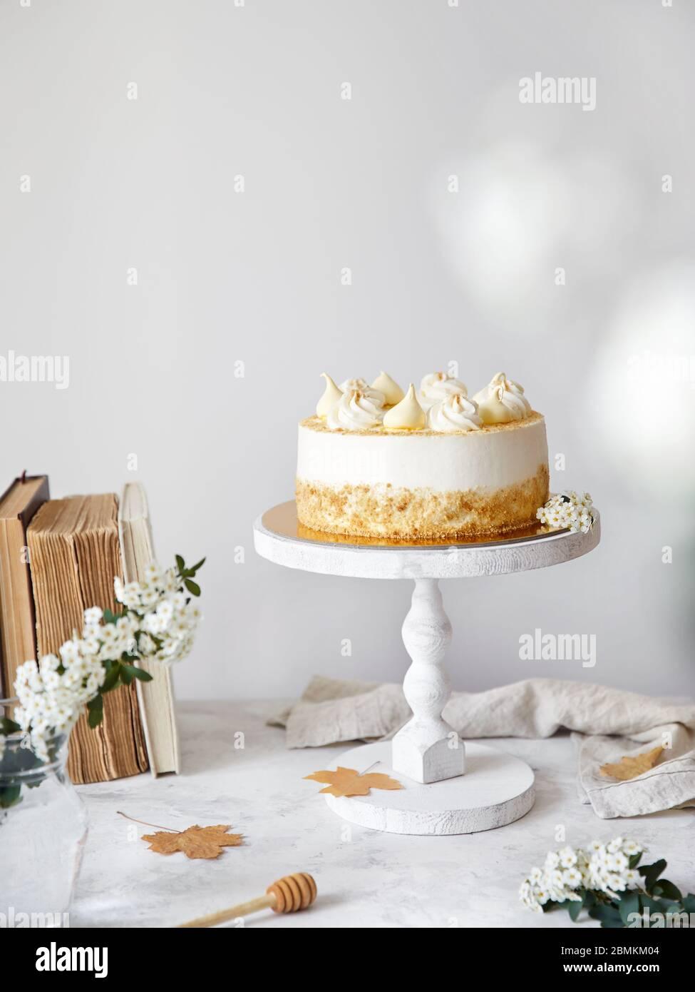 Pastel ruso casero con miel Medovik con crema y merengue en la parte superior. Flores blancas, hojas de otoño, libros viejos cerca en la mesa blanca Foto de stock