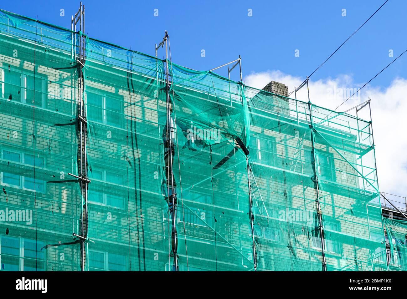 red de seguridad verde en andamios en la fachada de una casa de apartamentos Foto de stock
