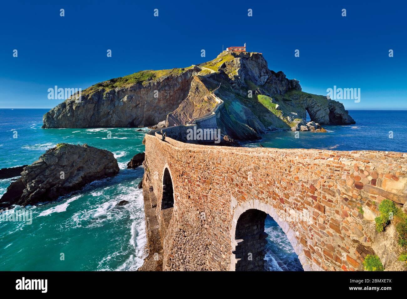 Puente de piedra arcada que conduce a una pequeña isla rocosa con una pequeña capilla en la parte superior Foto de stock