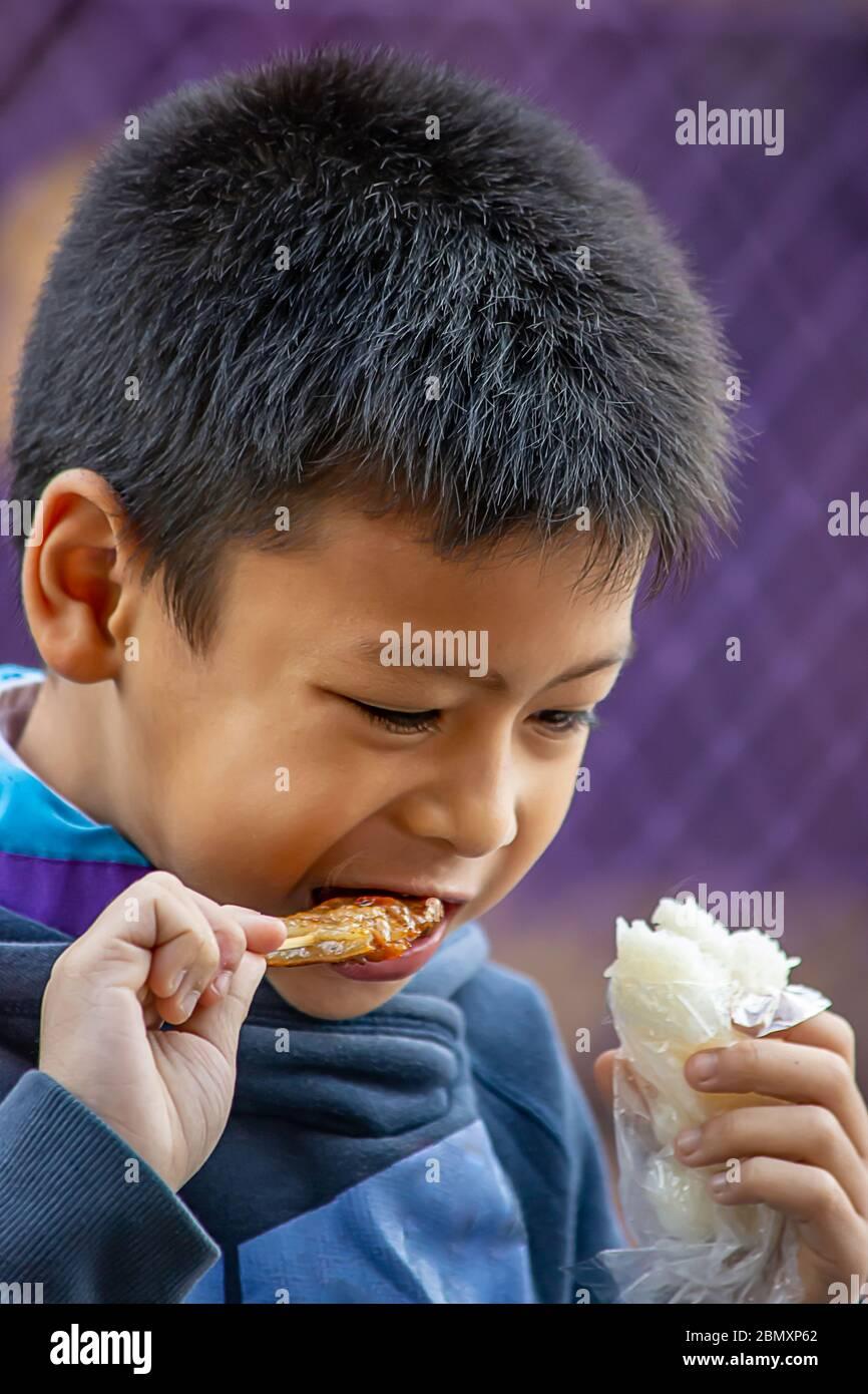Los niños asiáticos están comiendo arroz pegajoso y el cerdo asado, la comida es sencilla y muy popular para comer el desayuno en Tailandia. Foto de stock