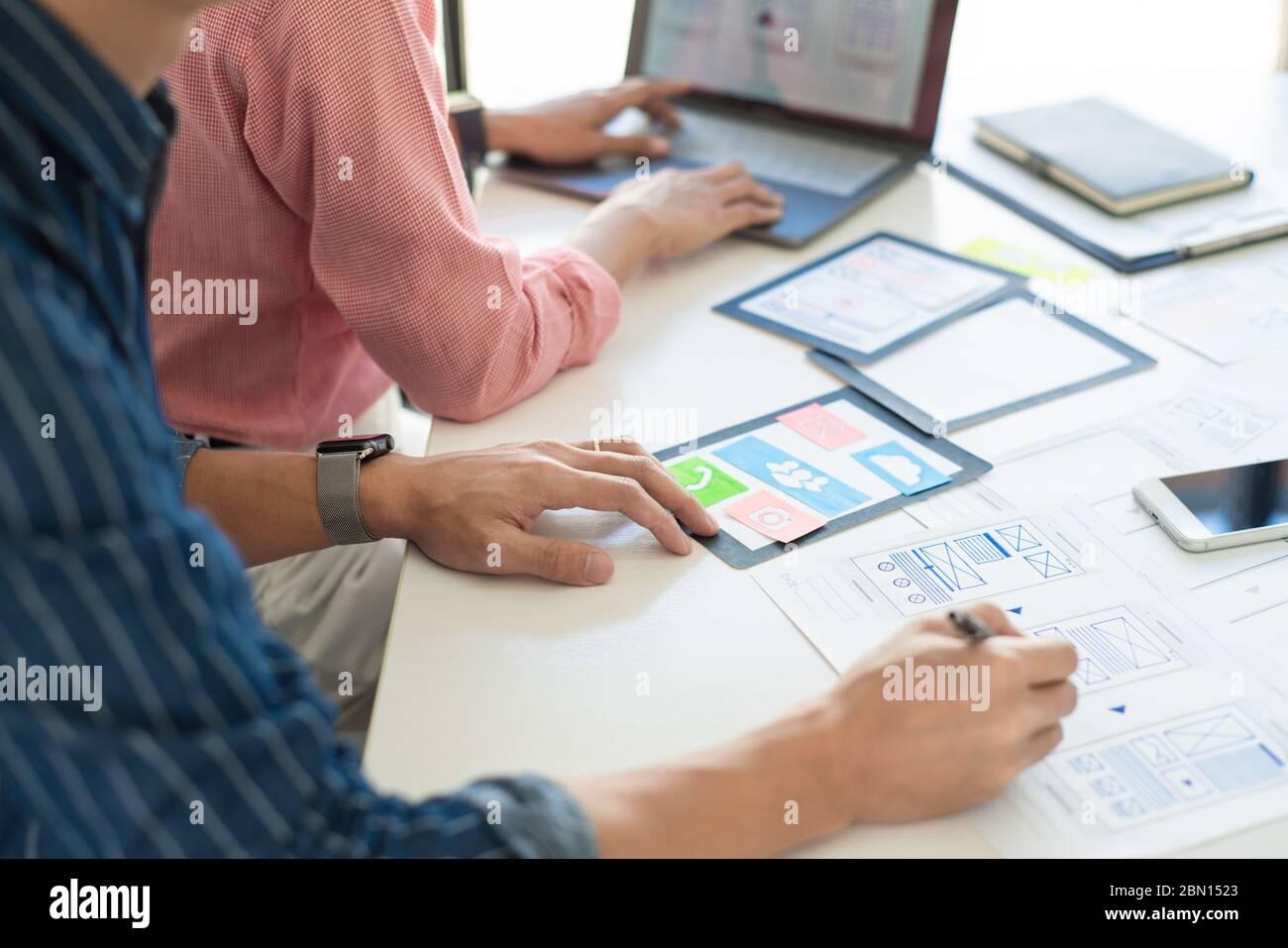 El equipo de diseñadores gráficos trabaja junto con el diseñador de la interfaz de usuario de UX de planificación de plantillas de aplicación de diseño de teléfono móvil prototipo, concepto de experiencia del usuario. Foto de stock