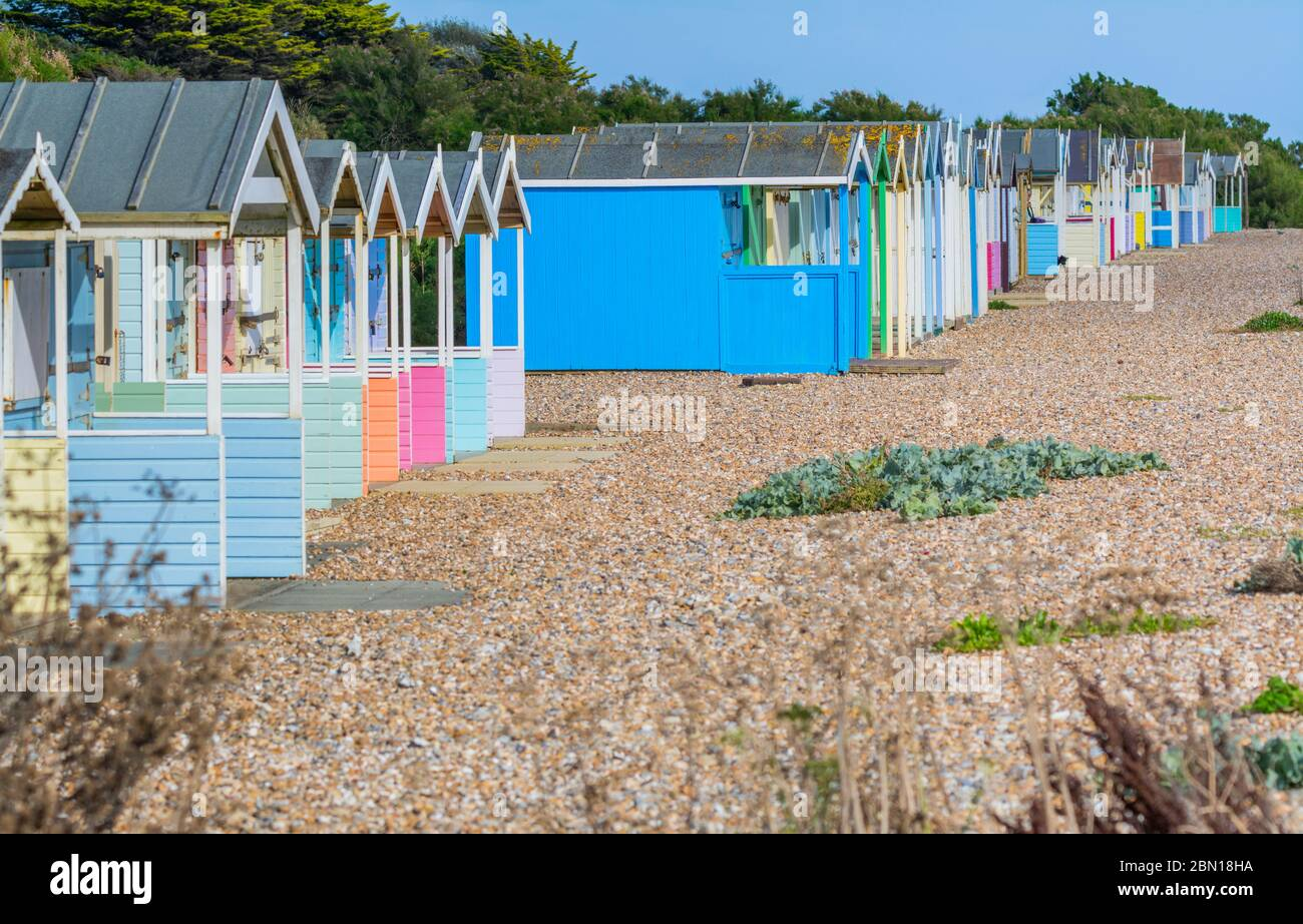 Fila de antiguas cabañas de playa multicolor en una playa de guijarros en Rustington, West Sussex, Inglaterra, Reino Unido. Foto de stock