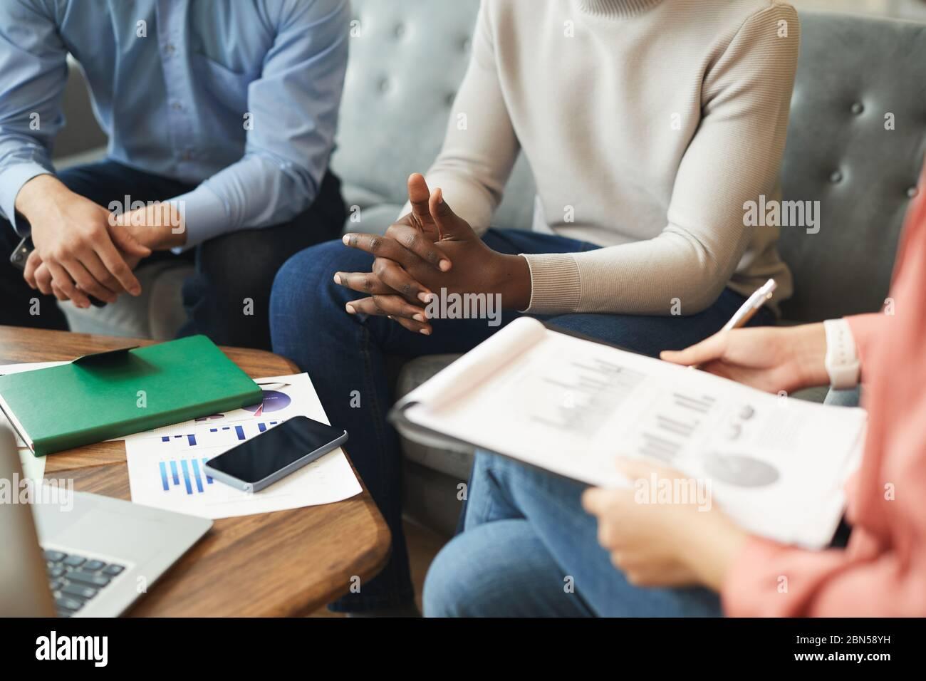 Vista en ángulo alto de una empresaria irreconocible que mantiene el portapapeles con el gráfico de datos mientras discute el proyecto de inicio con el equipo en la oficina, espacio de copia Foto de stock