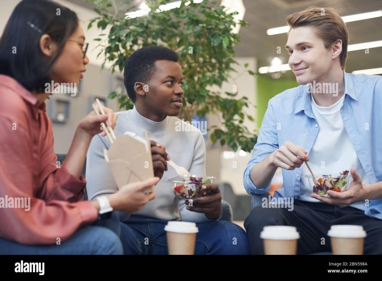 Grupo multiétnico de jóvenes comiendo comida para llevar y sonriendo durante el descanso de almuerzo en la escuela u oficina Foto de stock