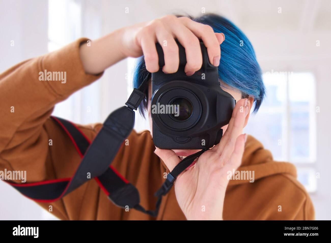 hipster chica sosteniendo cámara y tomando fotos. primer plano de la mano de la joven con cámara profesional en el estudio. concepto del día de la fotografía mundial Foto de stock
