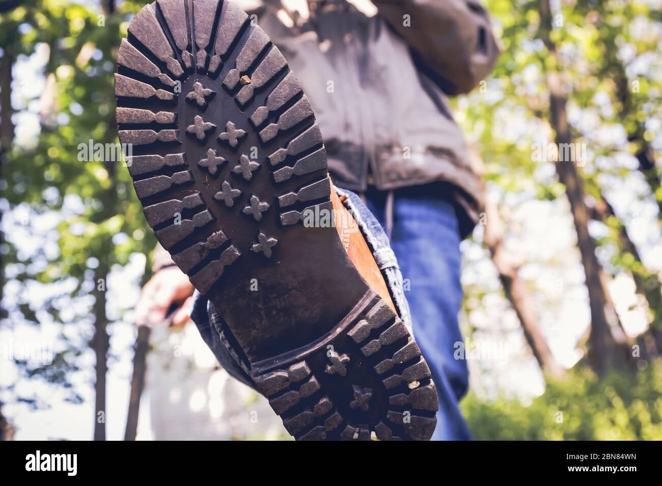Cerca de un hombre en botas caminando por el área del bosque Foto de stock