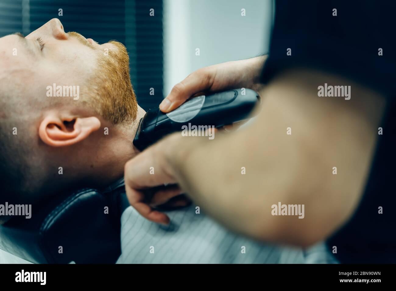 Barbería de corte barbudo hombre con máquina de afeitar en la peluquería. Proceso de peluquería. Primer plano de un estilista cortando la barba de un varón barbudo. Foto de stock