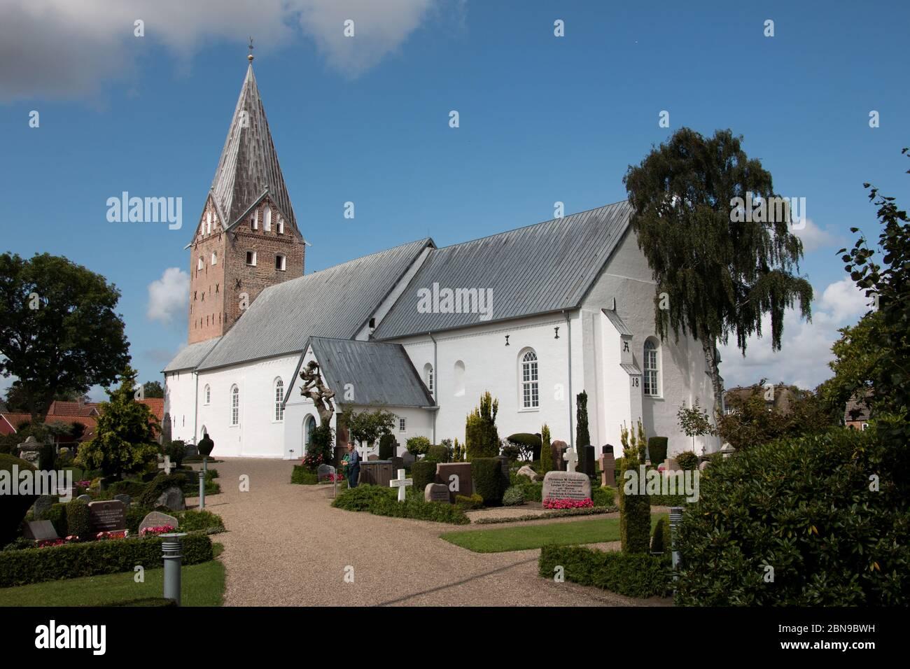 Tonder, Dinamarca - 20 de agosto de 2019: Mogeltonder iglesia con paredes blancas y un gran campanario y un cementerio a su alrededor en una pequeña ciudad de Dinamarca. Cátodo Foto de stock