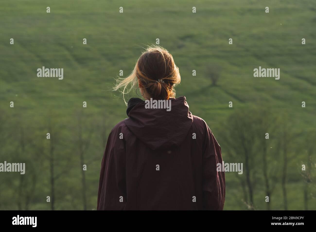 Detrás de una mujer de pie en las colinas en clima ventoso. Caminar, hacer senderismo y pasar tiempo libre al aire libre, portait adulto joven Foto de stock