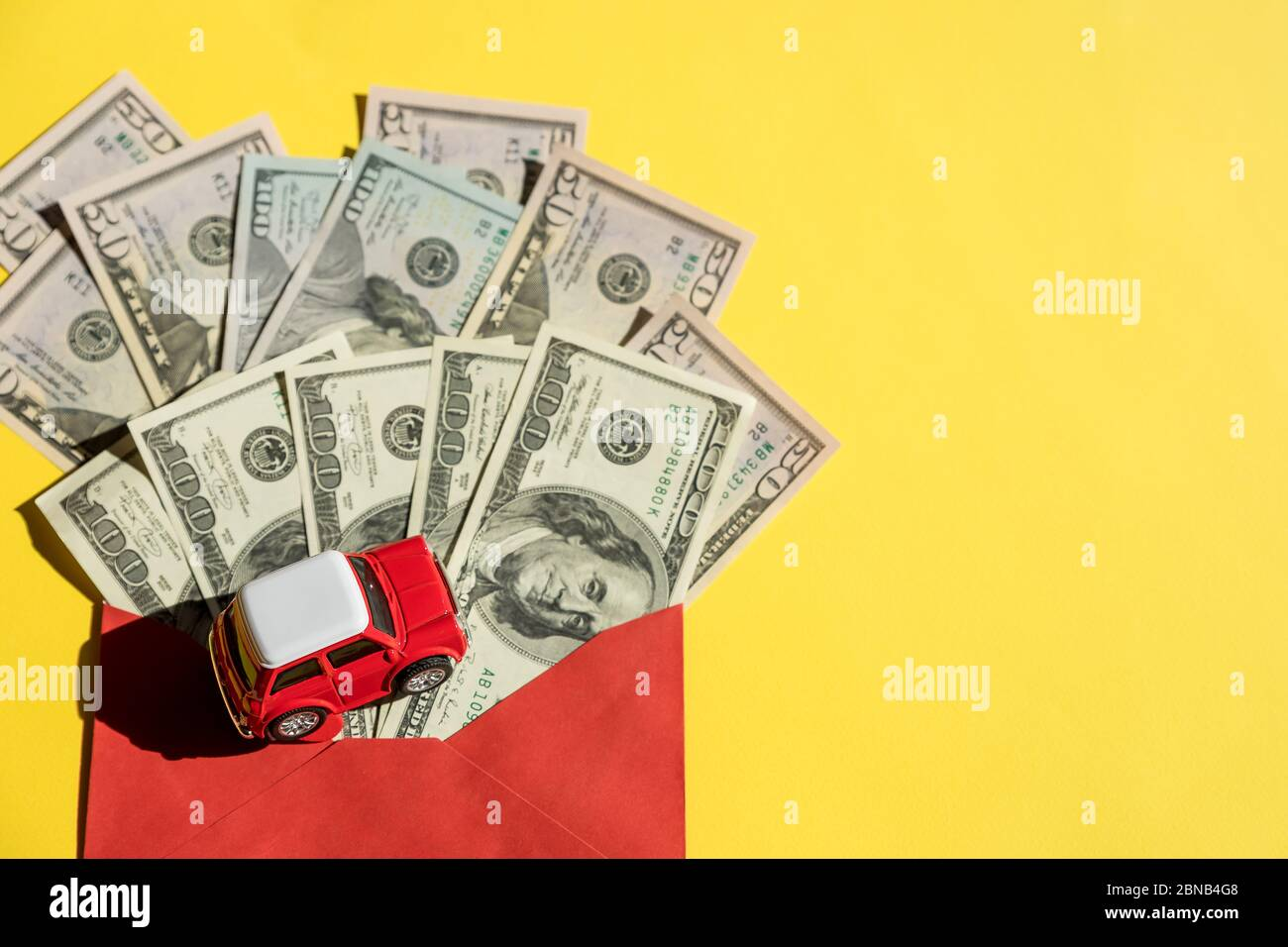 Modelo de coche y billetes de EE.UU., moneda. Préstamo de coche, financiero, ahorro de dinero, seguros y tiempo de leasing Concepts.toy coche rojo y un bote de dinero dólares facturas Foto de stock