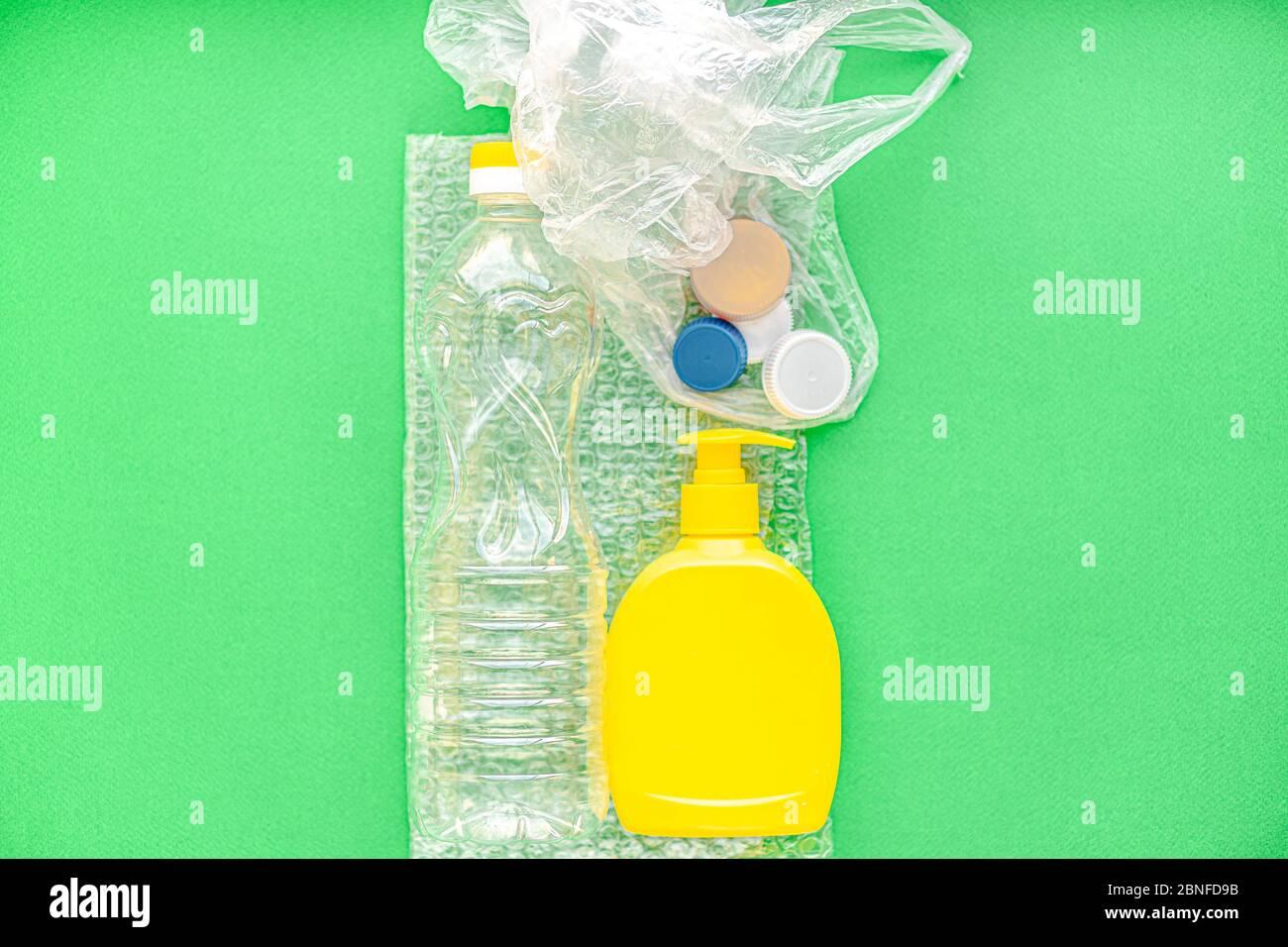 concepto de basura, ecología, separación de basura - disposición de la clasificación de residuos en diferentes tipos de plástico en un espacio de copia de fondo verde. Foto de stock