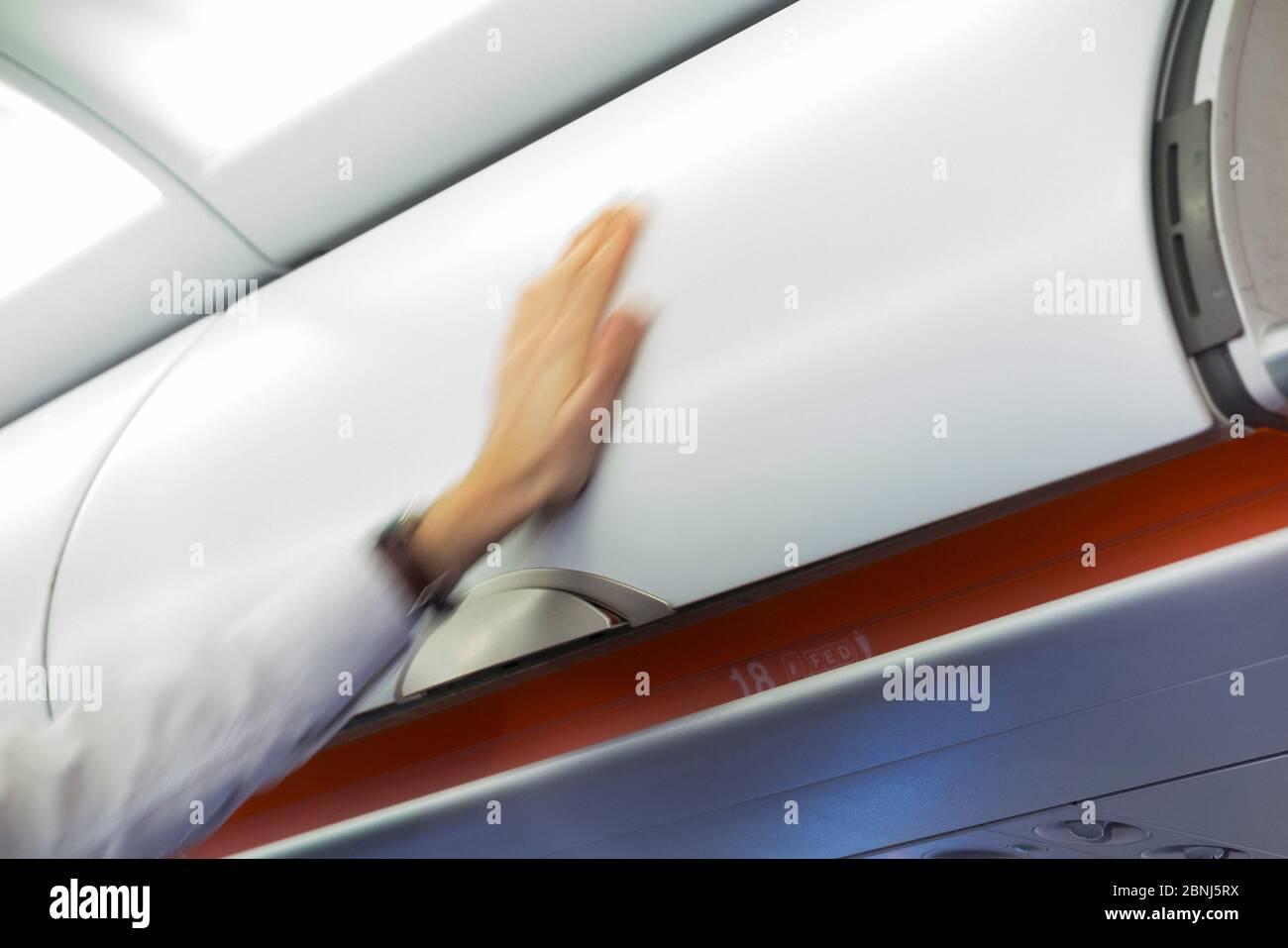 El miembro del asistente de vuelo de la tripulación de cabina cierra el avión aéreo sobre el depósito de equipaje / casilleros / compartimentos / puerta que contiene las bolsas de mano de los pasajeros. (115) Foto de stock