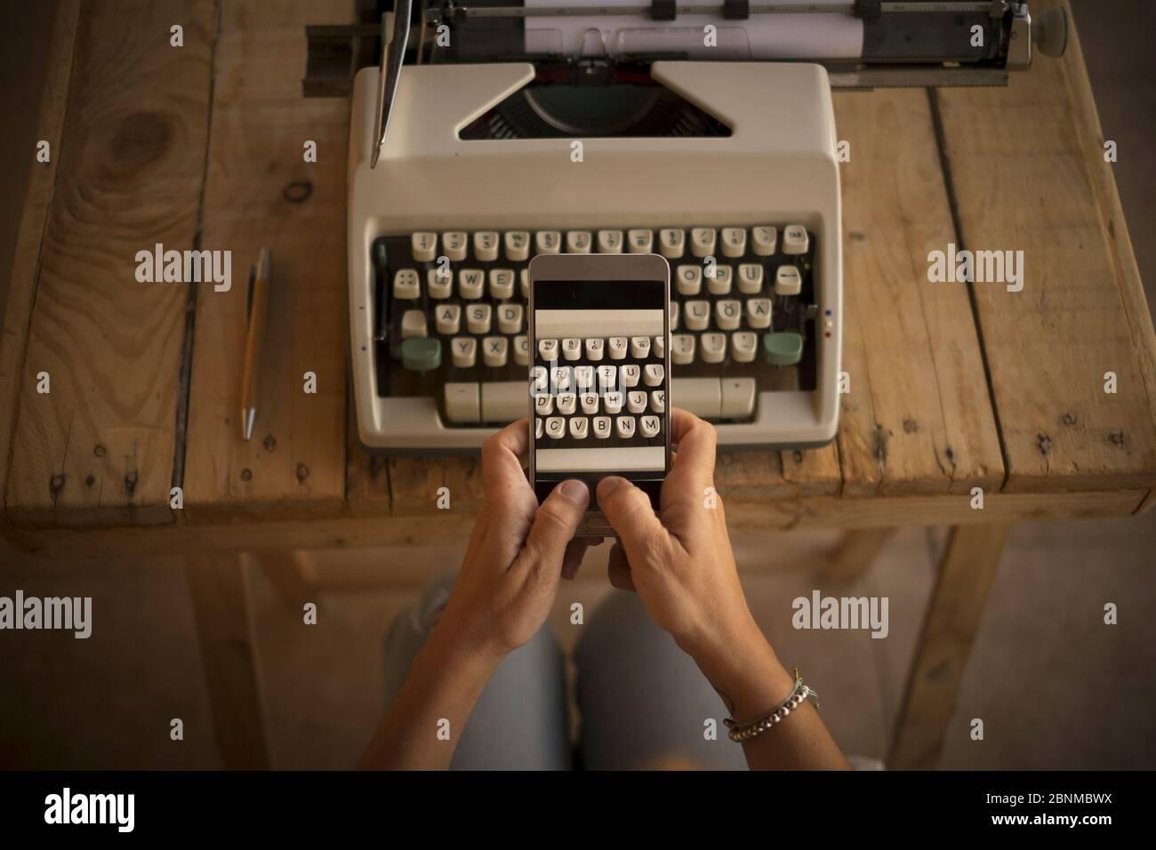 Concepto, escribir y trabajar con la vieja y moderna, nueva tecnología, la mujer toma una foto de una máquina de escribir con su teléfono celular Foto de stock