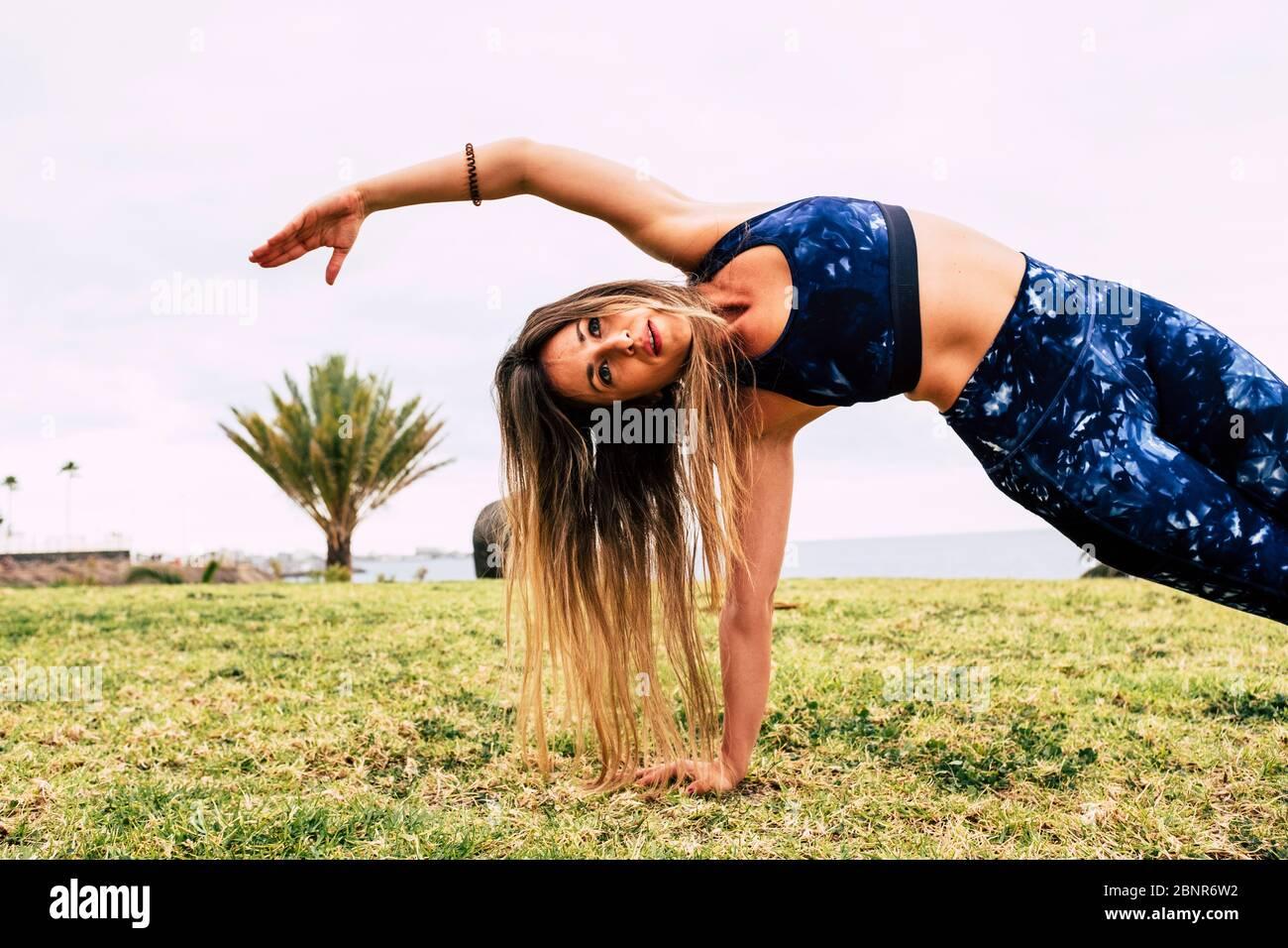 Concepto. De deporte y ejercicios de pérdida de peso - joven mujer caucásica gente haciendo pitas al aire libre en la naturaleza verde. Hierba sola - cuerpo perfecto y posición equilibrada Foto de stock