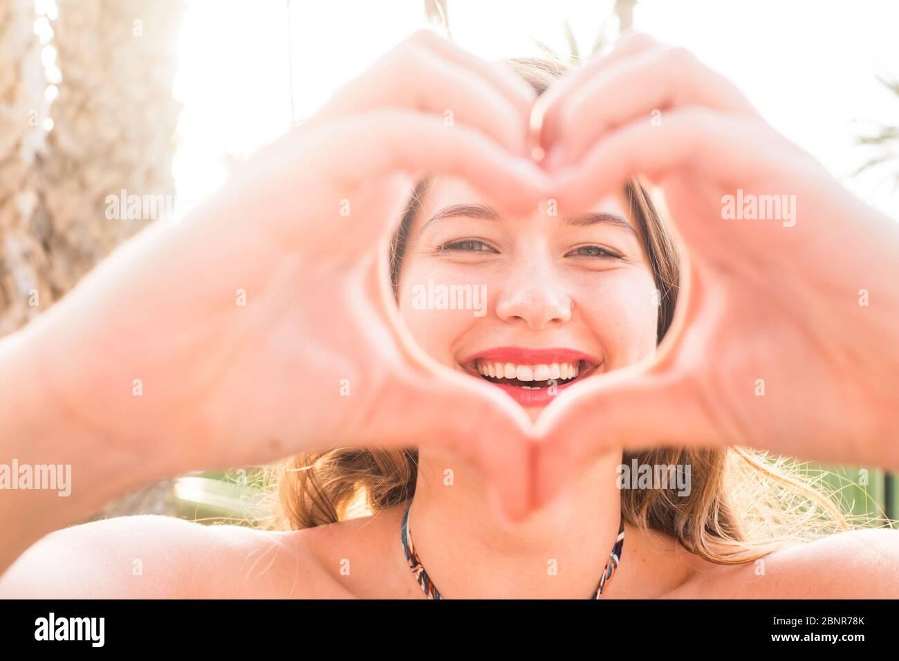 Retrato de cerca de hermosa. Mujer joven caucásica haciendo amor signo de corazón con las manos en la cámara - sol brillante fondo y felicidad alegre gente concepto Foto de stock