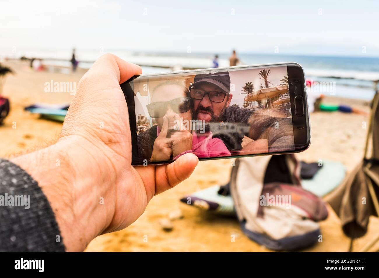 Un par de adultos locos y mujeres en la videollamada en la playa haciendo expresión divertida - gente feliz con tecnología teléfono hacer loco - alegría y buenos adultos en la playa durante las vacaciones Foto de stock