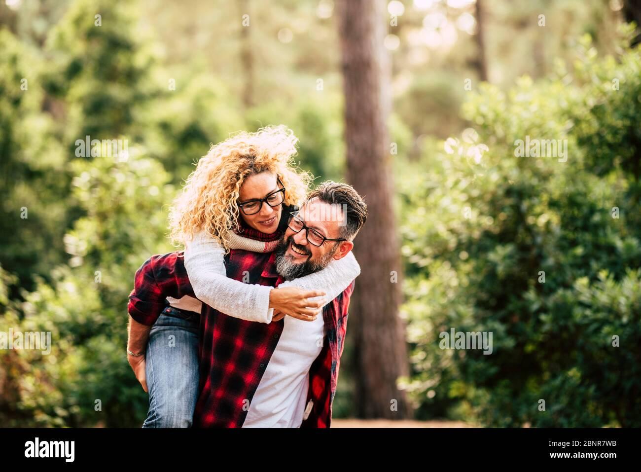 Feliz pareja caucásica adulta en relación y el amor jugar juntos en el bosque de la naturaleza - exterior personas de ocio actividad concepto con alegre caucásicos Foto de stock