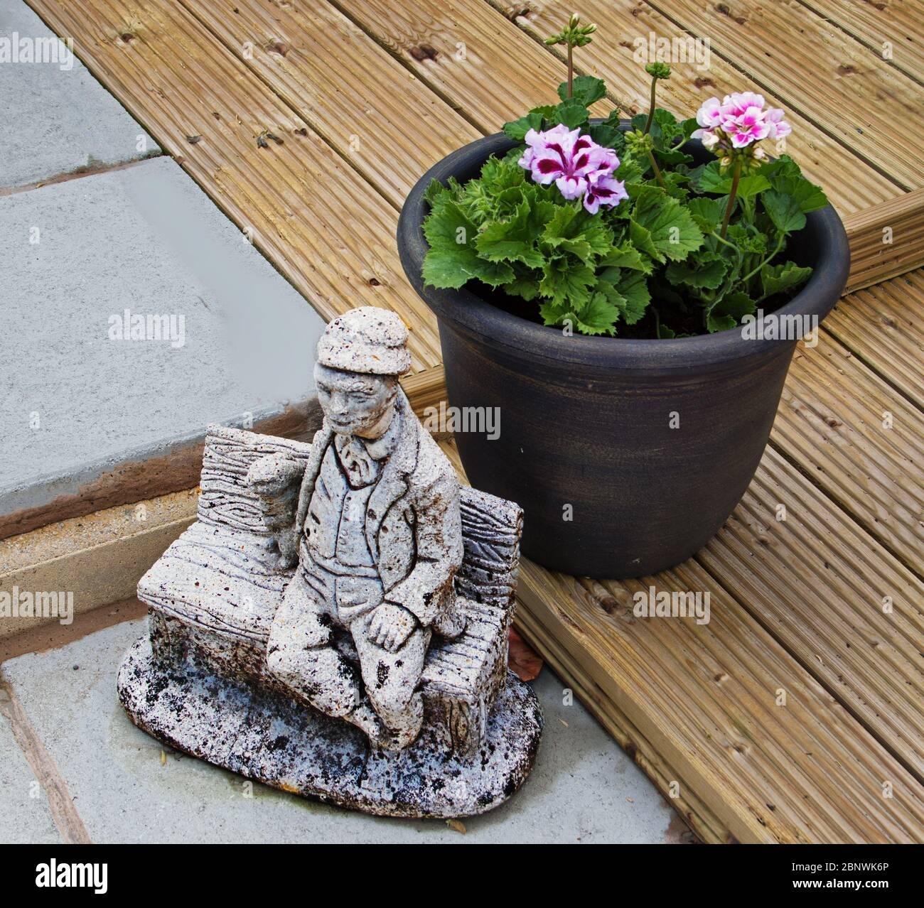 Un jardín, con un ornamento de características poner una maceta de planta en pavimento y tarima Foto de stock