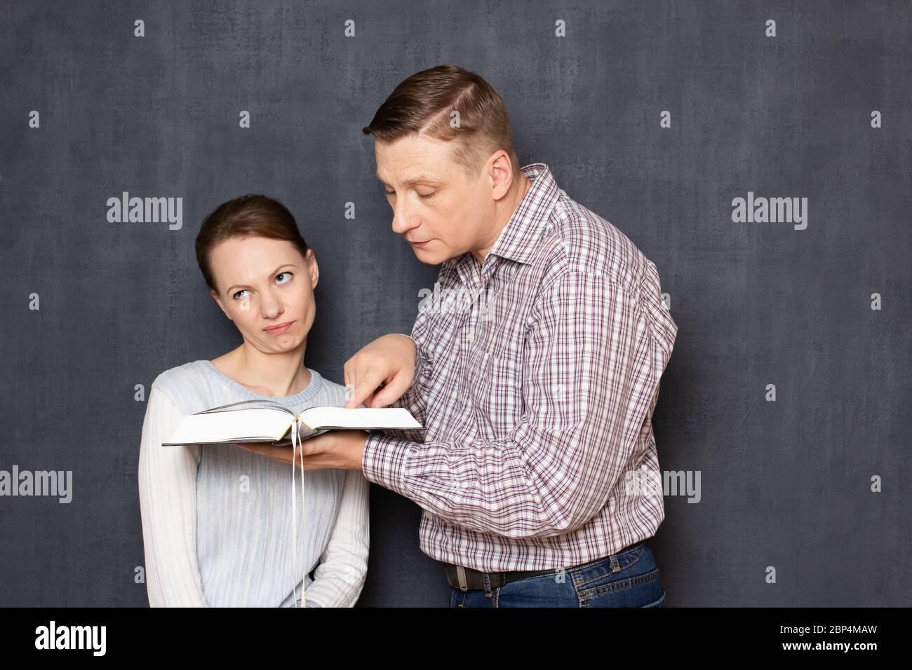 Estudio de un disparo de hombre tratando de prestar atención a la mujer disgustada a texto en el libro mientras está aburrida y cansada de leer y estudiar, no siendo internos Foto de stock