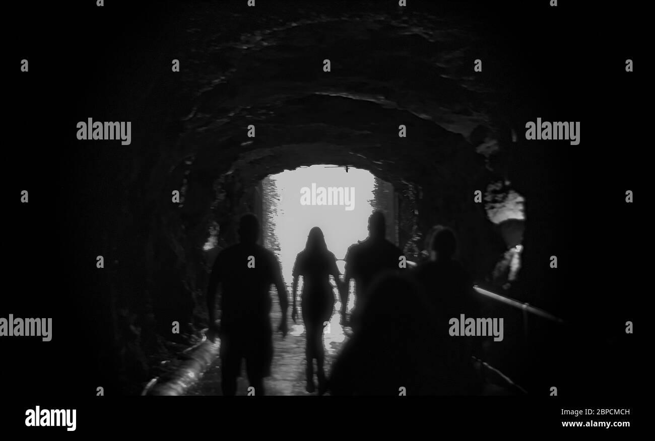 Siluetas caminando hacia la luz brillante como si pasaran a la vida después. Contraluz en blanco y negro imagen borrosa concepto de muerte y seguir adelante. Foto de stock