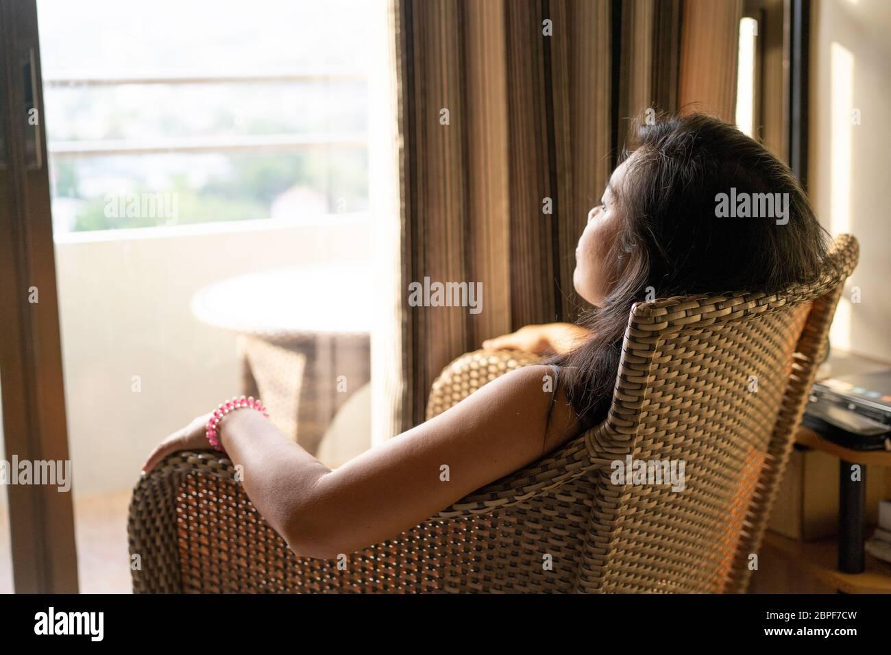 Imagen conceptual de los problemas relacionados con la salud mental.UNA mujer sentada en una silla se mira de una ventana abierta durante un período de cuarentena en la pandemia COVID-19 2020 Foto de stock