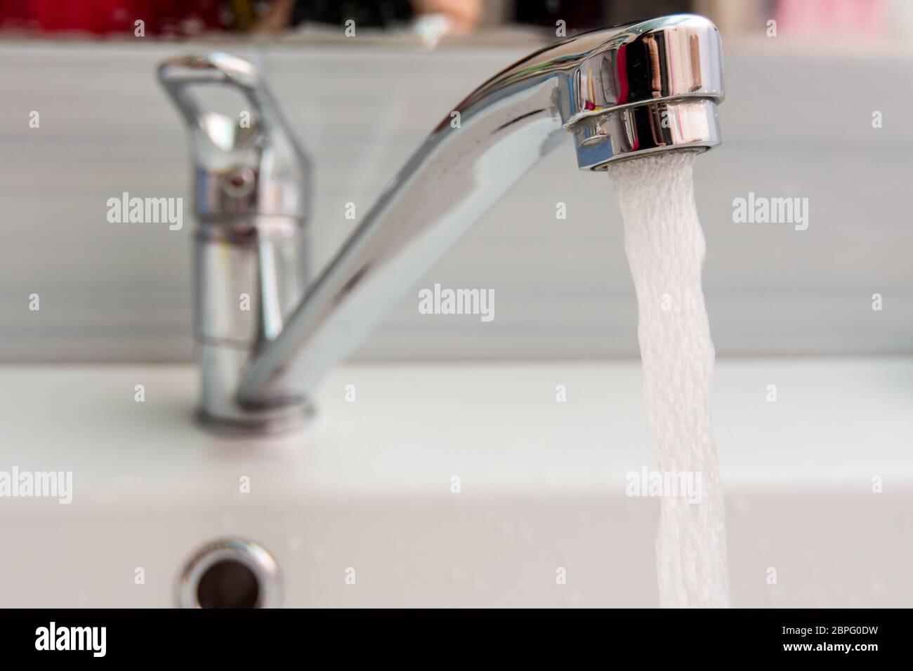 El agua fluye más presión desde el mezclador en el baño Foto de stock