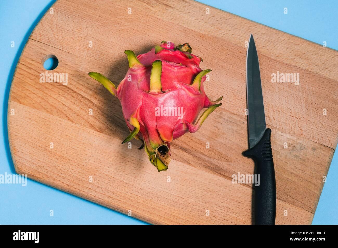 Pitaya madura y un cuchillo en una tabla de cortar. Corta la pitaya a la mitad. Fruta de dragón de verano. Vista superior de un diseño plano. Foto de stock