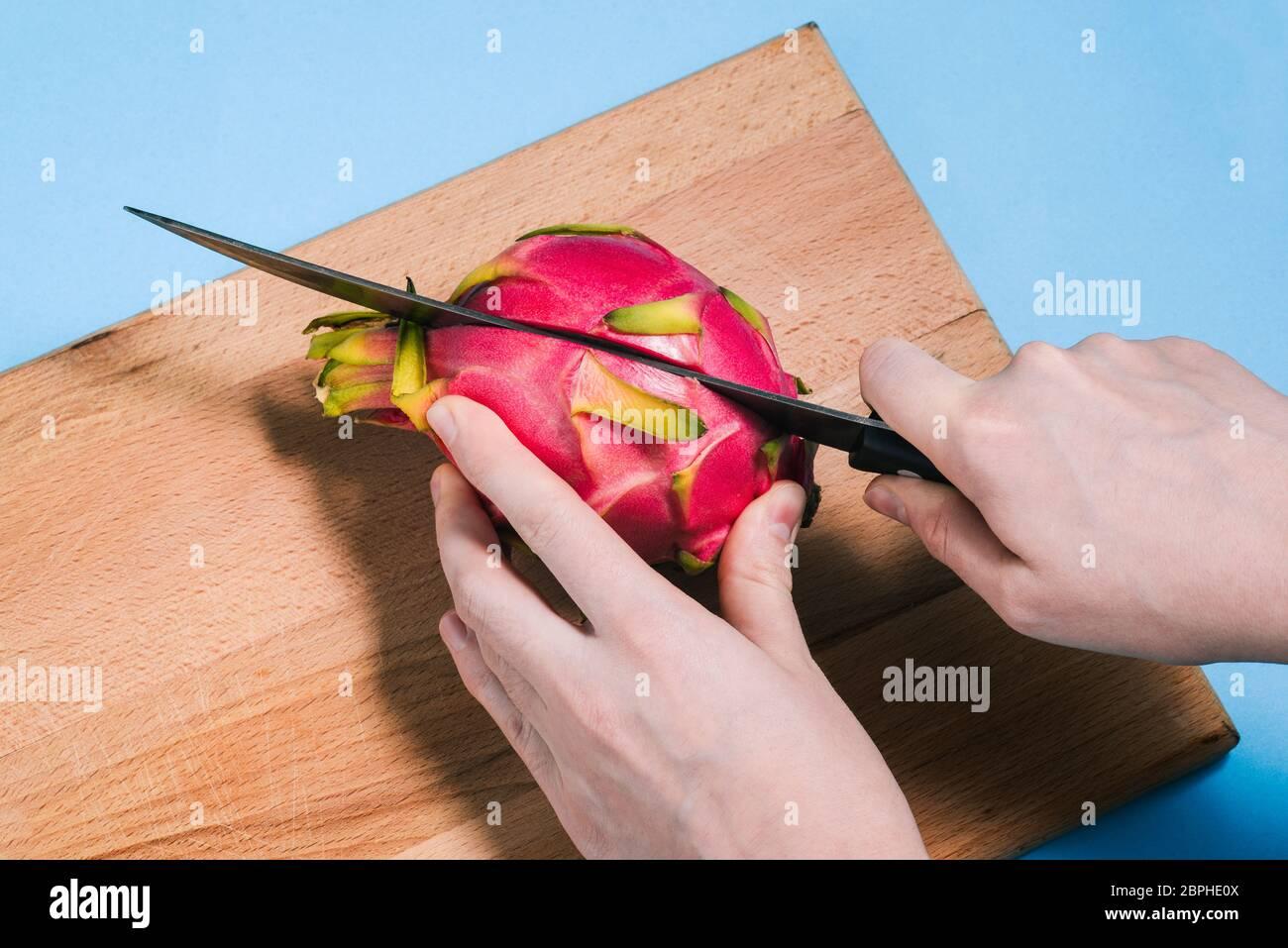 Primer plano de las manos de una mujer cortando una fruta madura de pitaya con un cuchillo en una tabla de madera. Pattaya está cortado en dos partes. La vista desde arriba. Foto de stock