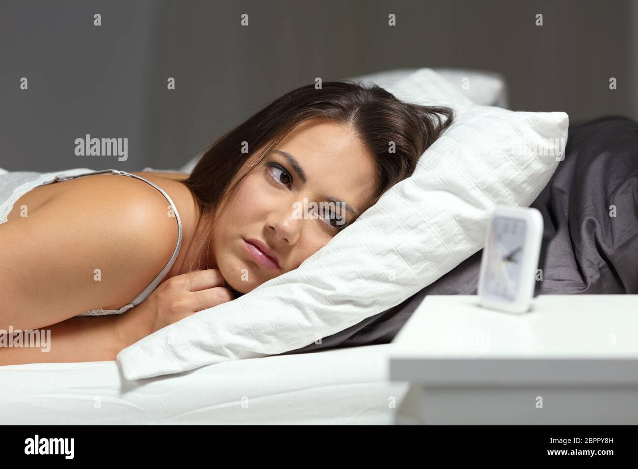 Sleepless insomniac chica mirando el despertador tumbado en la cama en la noche en su domicilio. Foto de stock