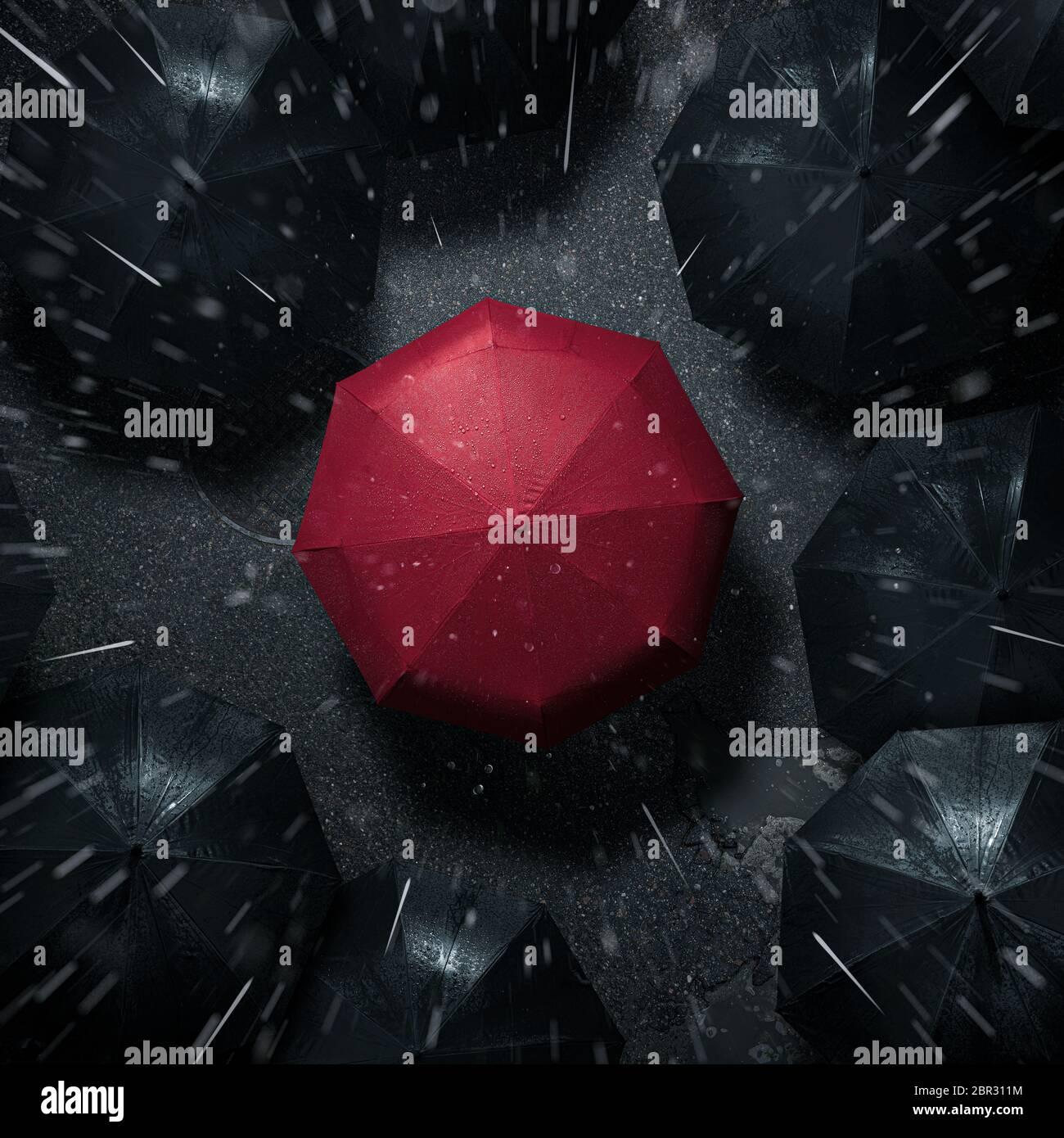 Desde la multitud, vista en ángulo alto de paraguas rojo entre muchos oscuros en la lluvia Foto de stock
