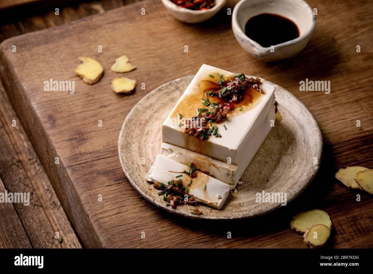 Queso De Soja Japones De Seda Tofu Pedazo Entero Con Jengibre De Chile Cebolleta Y Salsa De Soja Que Se Reparte Sobre Una Placa De Ceramica Sobre Una Mesa De Madera Fotografia