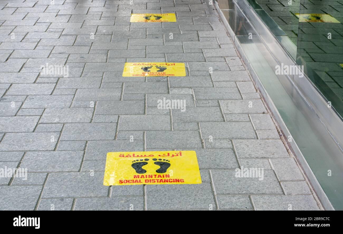 Mantener pegatinas de distanciamiento social pegadas en el piso frente al restaurante en Qatar Foto de stock